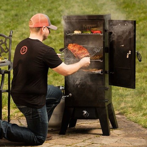 Ruben using a gas smoker in the backyard of his home.