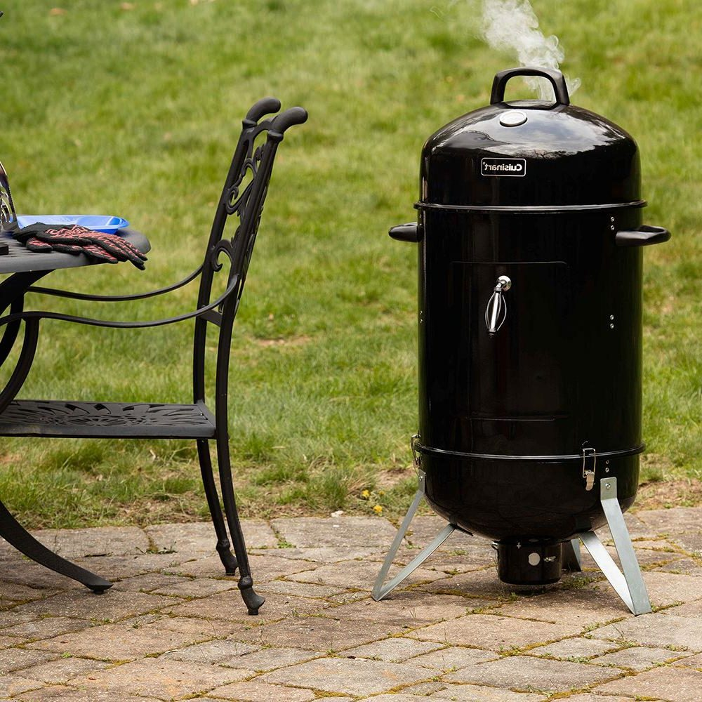 A charcoal smoker in the yard.